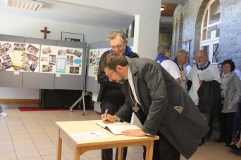 Mgr Delville signe le livre d'or - Exposition 80 ans de pèlerinage liégeois à Banneux