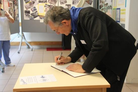 Mgr Jousten signe le livre d'or - Exposition 80 ans de pèlerinage liégeois à Banneux